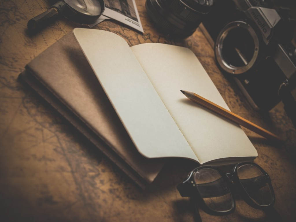 Picture of a blank journal with pencil, eye glasses and camera.